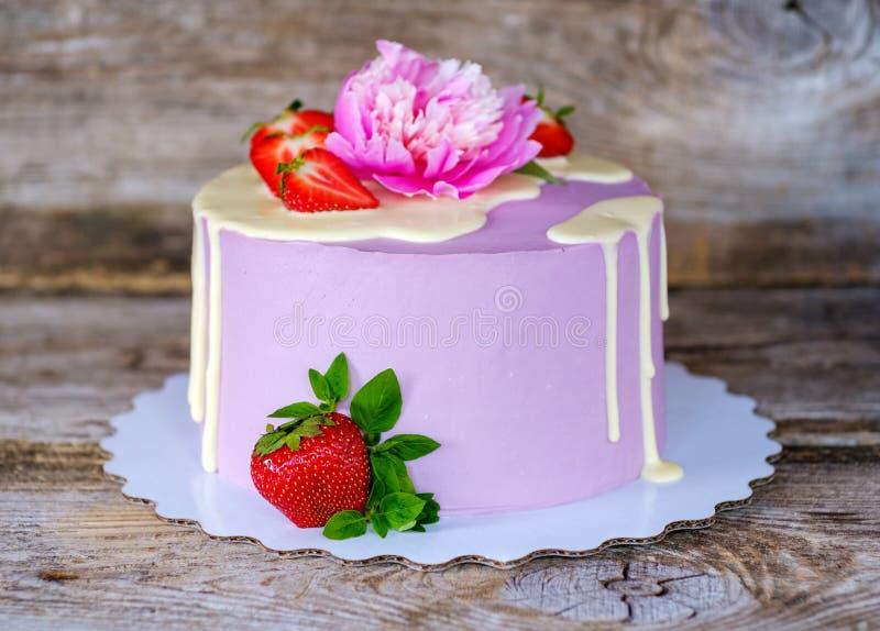 Mooie eigengemaakte cake met purpere room en levende pioen stock afbeelding