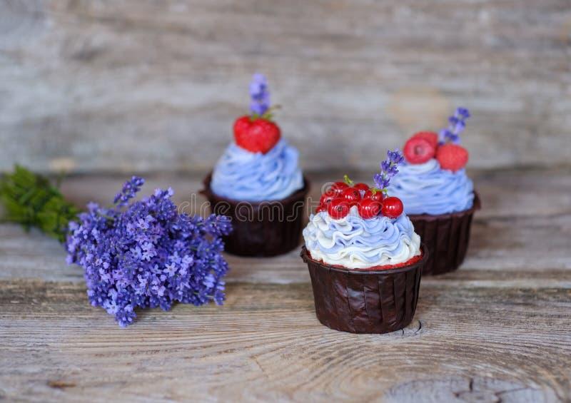Mooie eigengemaakte cupcakes met purpere room en een boeket van lavendel stock foto's