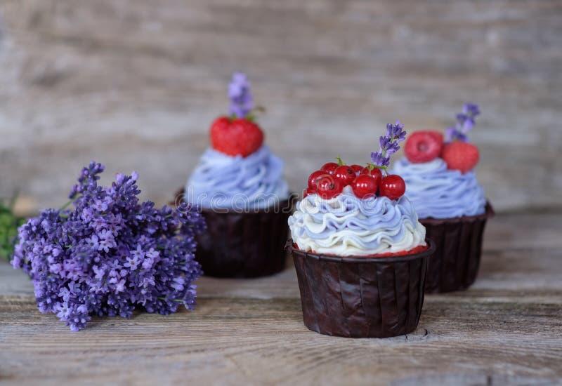 Mooie eigengemaakte cupcakes met purpere room en een boeket van lavendel royalty-vrije stock foto's