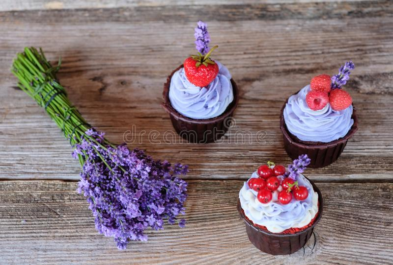 Mooie eigengemaakte cupcakes met purpere room en een boeket van lavendel stock afbeelding