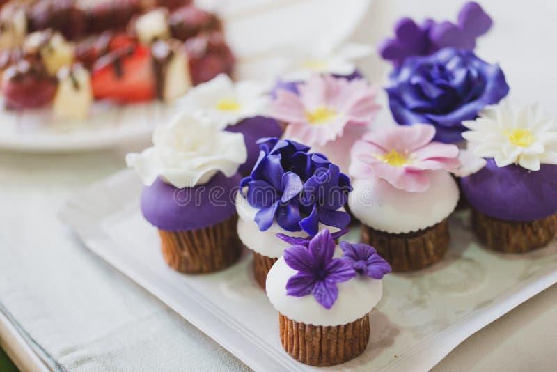 Mooie eigengemaakte cupcakes met purpere, witte en roze marsepein bloeit op bovenkant royalty-vrije stock foto's