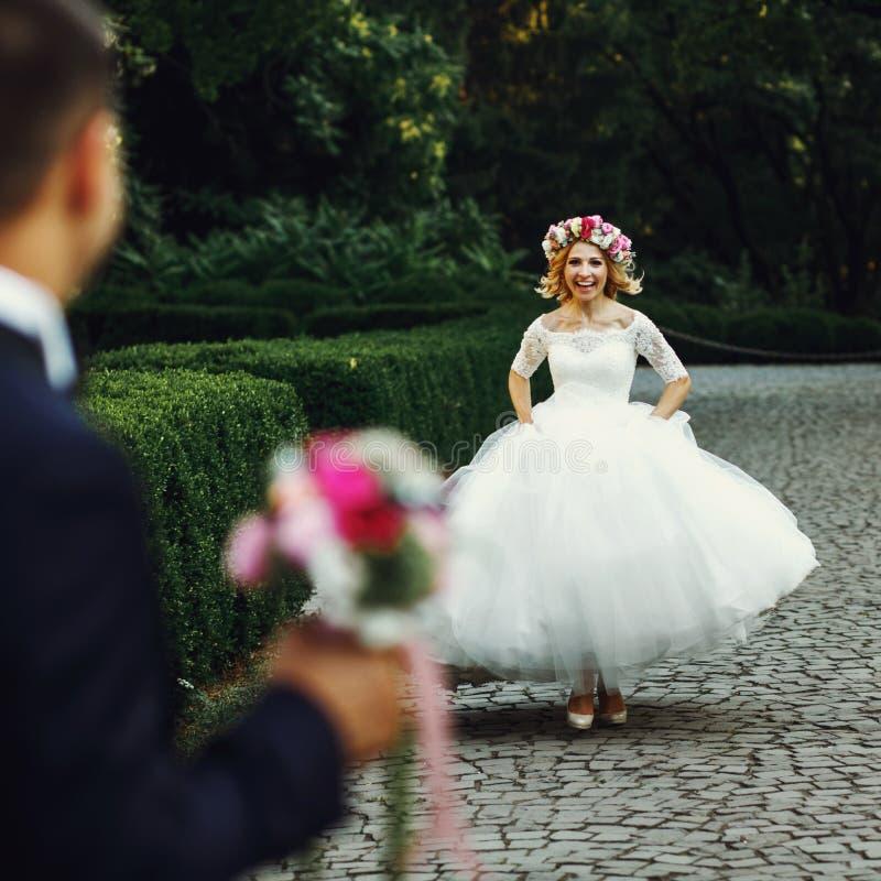 Mooie elegante blondebruid die naar het charmeren van bruidegomou lopen royalty-vrije stock foto