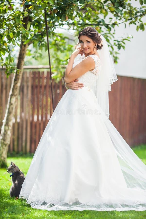 Mooie elegante gelukkige donkerbruine bruid op de achtergrond groen g royalty-vrije stock afbeeldingen