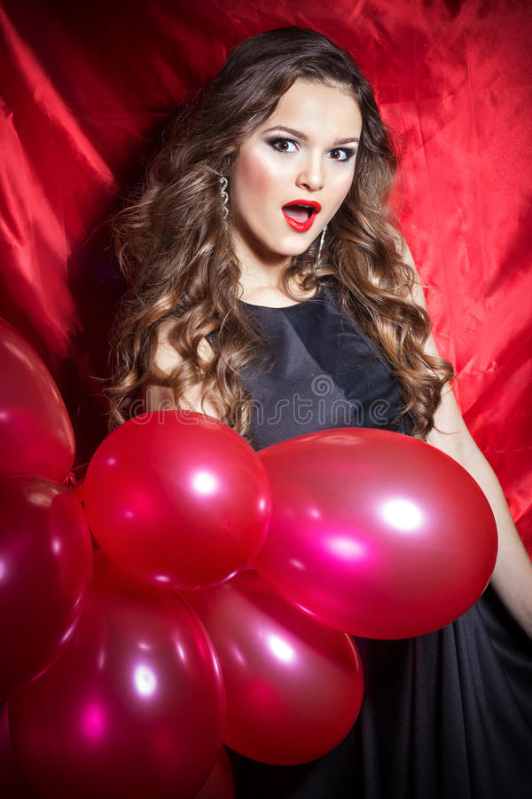 Mooie elegante gelukkige jonge vrouw met rode ballen in handen met rode lippenstift stock afbeelding
