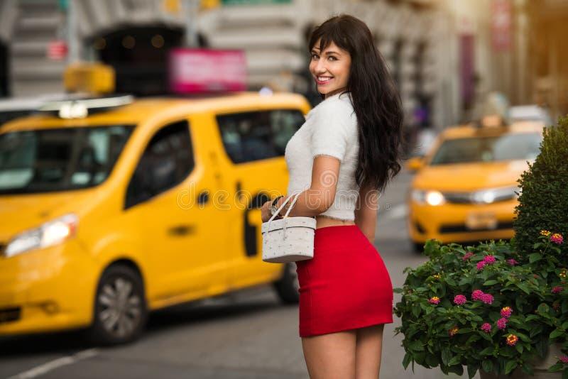 Mooie elegante glimlachende vrouw die aan gele taxi op stadsstraat lopen van New York royalty-vrije stock afbeelding