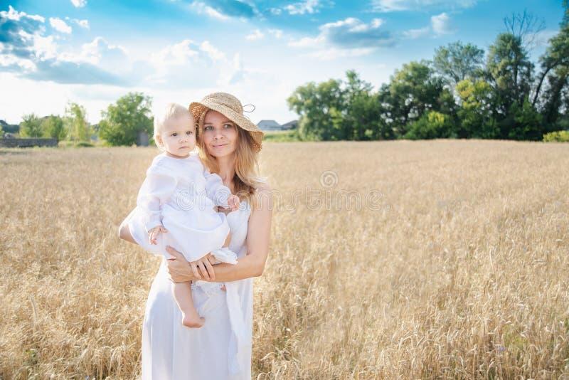 Mooie elegante moeder en weinig gebied van de dochtertarwe, familie royalty-vrije stock foto