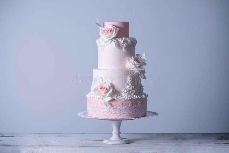 Mooie elegante vier tiered roze die huwelijkscake met rozenbloemen wordt verfraaid Concept bloemen van suikermastiek royalty-vrije stock foto's