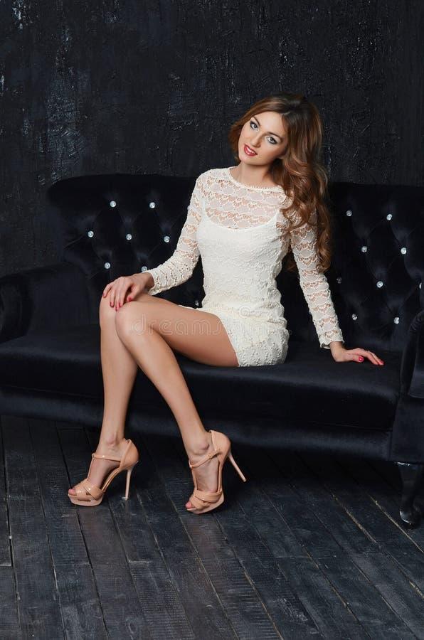 Mooie elegante vrouw in een zwart binnenland stock foto
