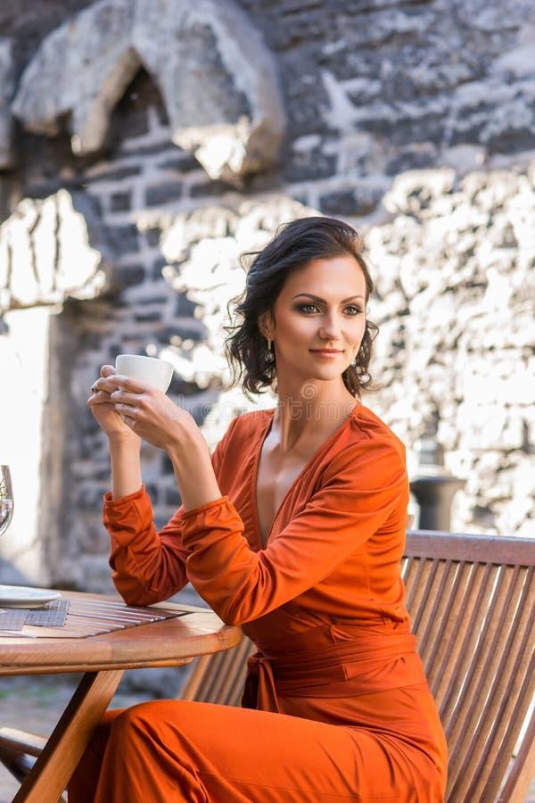 Mooie elegante vrouw in oranje robe het drinken koffie stock afbeeldingen