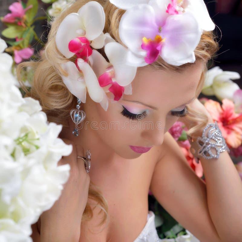 Mooie elegante vrouw rond de bloemen. royalty-vrije stock afbeelding