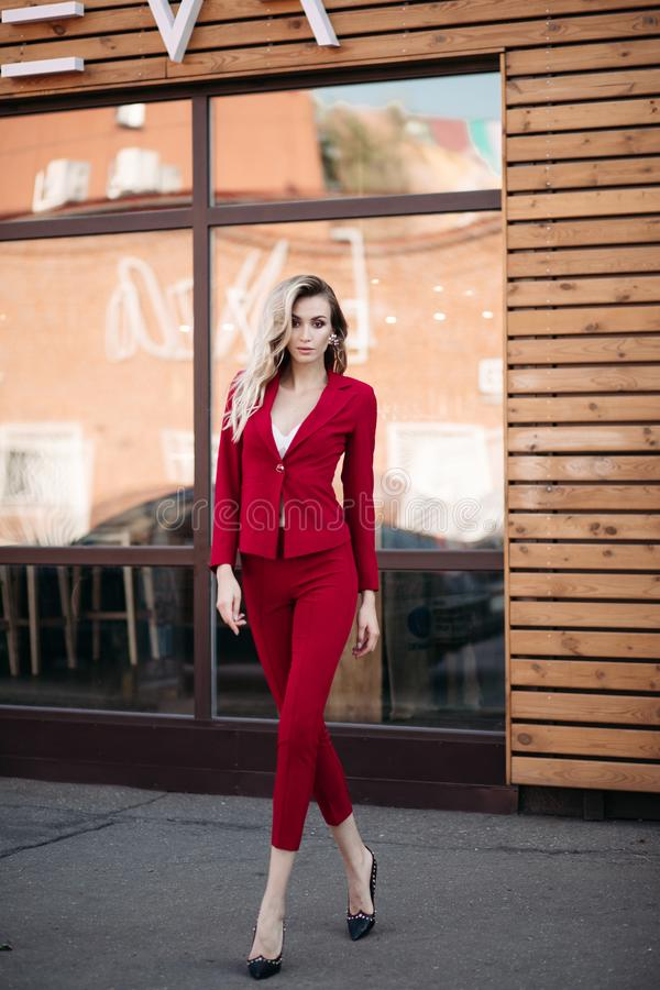 Mooie elegantie modieuze dame in rood kostuum en zwarte schoenen die bij camera stellen stock afbeelding