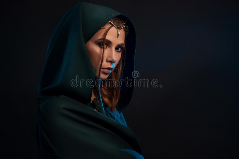 Mooie elfprinses die donkergroene kaap dragen die camera van duisternis bekijken stock fotografie