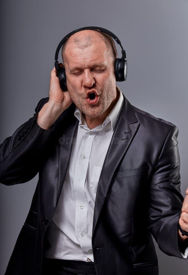 Mooie emotionele dansende en zingende kale mens die de muziek in draadloze hoofdtelefoon op donkere grijze achtergrond luisteren  stock foto's