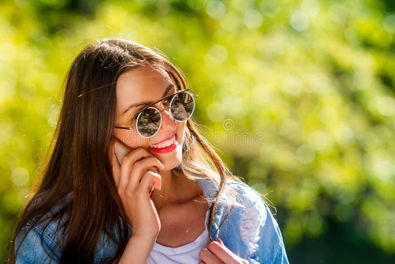 Mooie, emotionele, jonge vrouw in zonnebril die op de telefoon spreken Zachte Achtergrond De ruimte van het exemplaar stock foto
