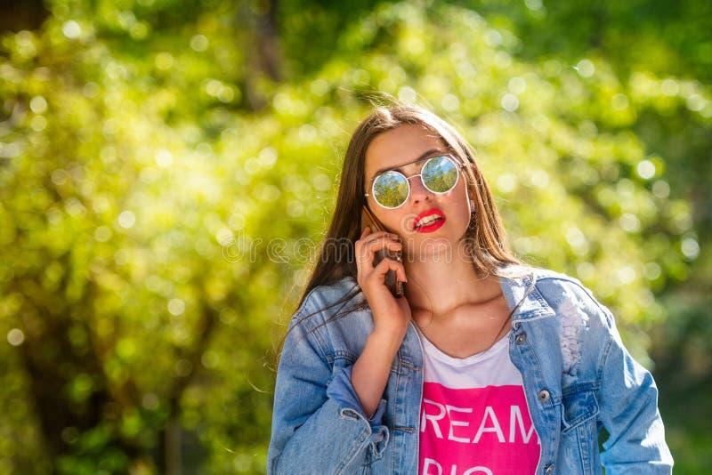 Mooie, emotionele, jonge vrouw in zonnebril die op de telefoon spreken Zachte Achtergrond De ruimte van het exemplaar stock afbeelding