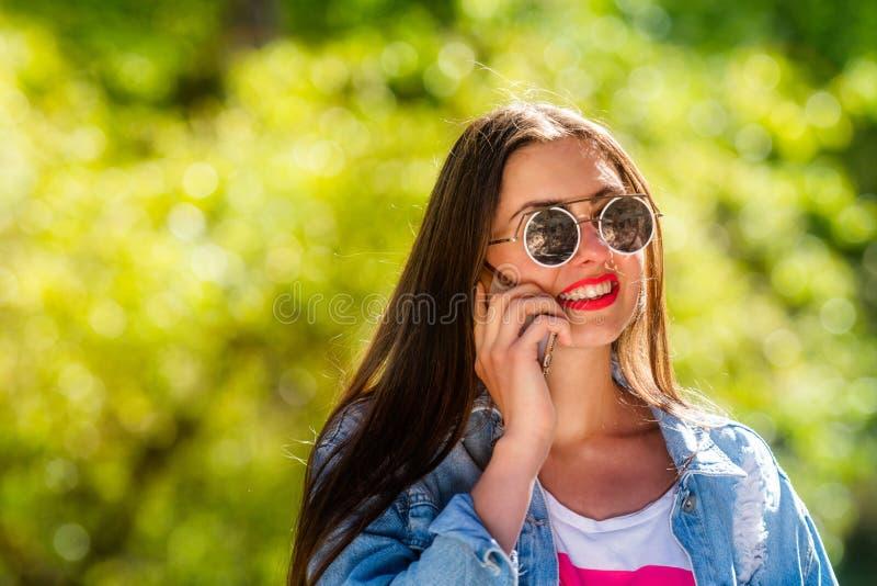 Mooie, emotionele, jonge vrouw in zonnebril die op de telefoon spreken Zachte Achtergrond De ruimte van het exemplaar royalty-vrije stock afbeeldingen