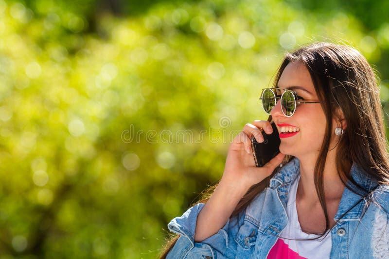 Mooie, emotionele, jonge vrouw in zonnebril die op de telefoon spreken Zachte Achtergrond De ruimte van het exemplaar stock afbeeldingen