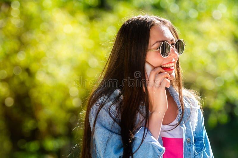 Mooie, emotionele, jonge vrouw in zonnebril die op de telefoon spreken Zachte Achtergrond De ruimte van het exemplaar royalty-vrije stock fotografie