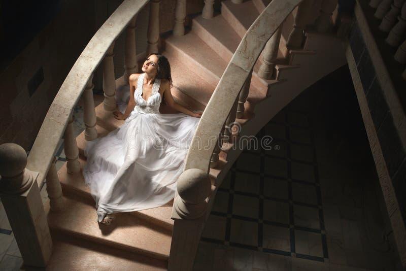 Mooie, emotionele, sexy dame, vrouwenzitting op treden in dark royalty-vrije stock afbeeldingen