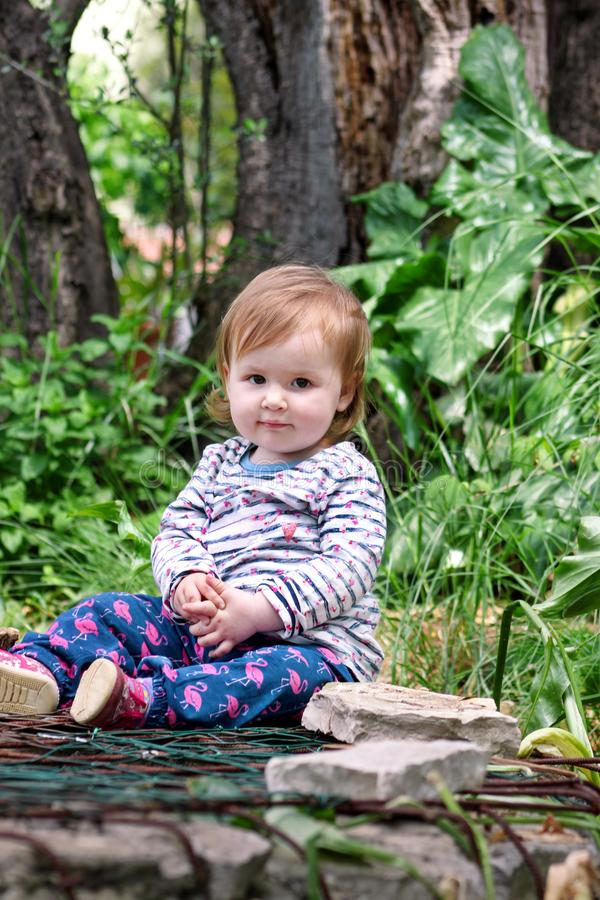 Mooie en babyzitting die, die portret glimlachen stellen Weinig leuk meisje is speels in tuin Het kind speelt buiten in park stock afbeeldingen