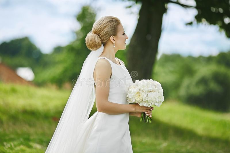 Mooie en elegante jonge blondevrouw in modieuze huwelijkskleding met boeket van witte bloemen in haar handen die in openlucht ste royalty-vrije stock afbeelding