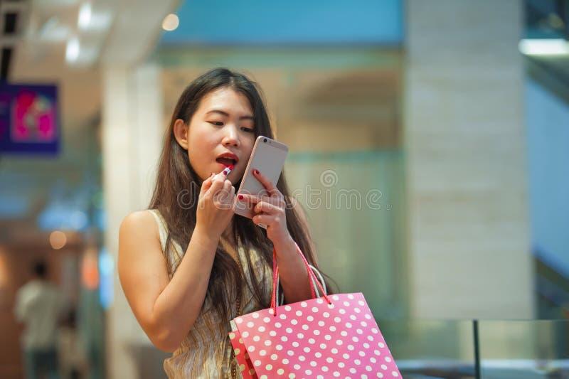 Mooie en gelukkige Aziatische Chinese vrouw die lippen met lippenstiftmake-up retoucheren die mobiele telefoon bekijken die het g stock afbeelding