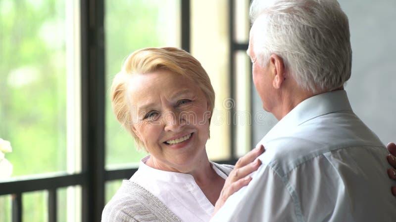 Mooie en gelukkige bejaarde paarbespreking en glimlach Vrouw die de camera bekijkt