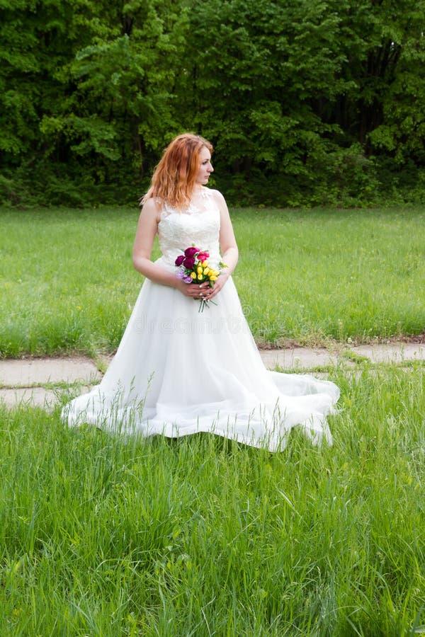 Mooie en gelukkige bruid op de bosrand royalty-vrije stock afbeeldingen