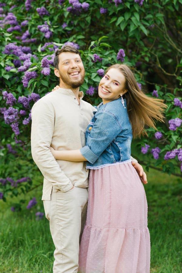 Mooie en gelukkige jongerenomhelzing elkaar in de tuin stock foto
