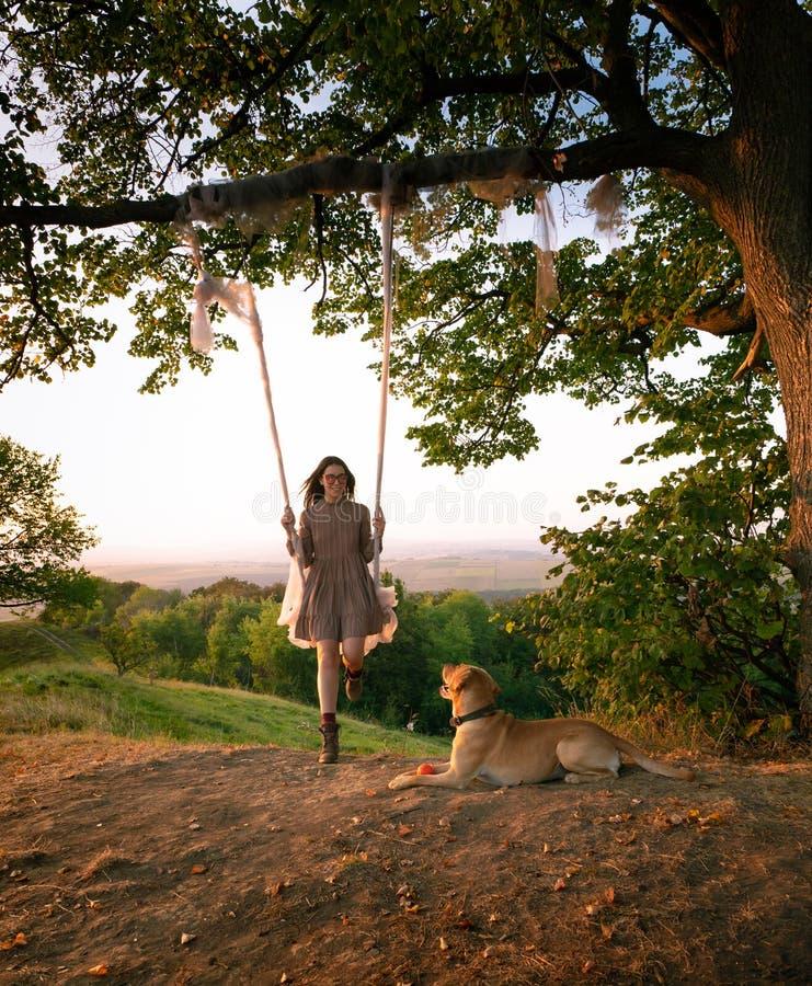 Mooie en gelukkige meisjesrit op een schommeling tegen de achtergrond van de stad naast een zittingshond royalty-vrije stock afbeelding