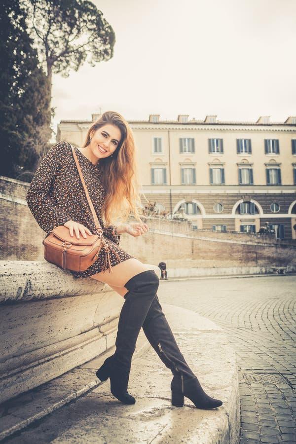 Mooie en glimlachende jonge vrouw in de straat in de stad royalty-vrije stock foto