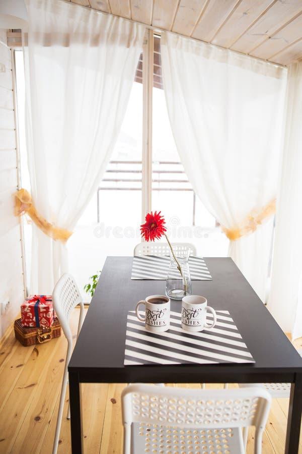 Mooie en heldere keukenstudio in de Skandinavische stijl, helder huis Vaas en een kop van koffie op de lijst stock afbeelding