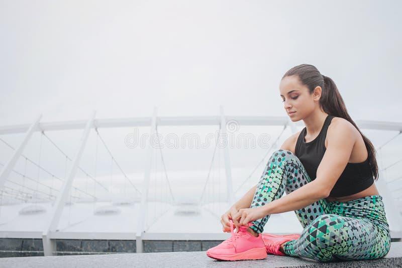 Mooie en mooie jonge vrouwenzitting en het hebben van rust bindt zij kant op haar sportenschoenen Modelglimlachen Zij is royalty-vrije stock afbeeldingen