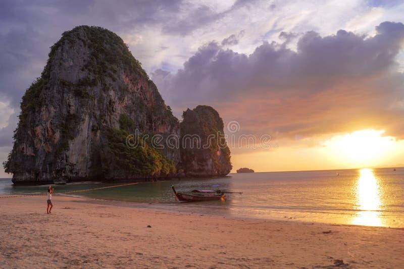 Mooie en kleurrijke zonsondergang bij het strand met rotsen, mensen en een boot in Thailand stock afbeelding
