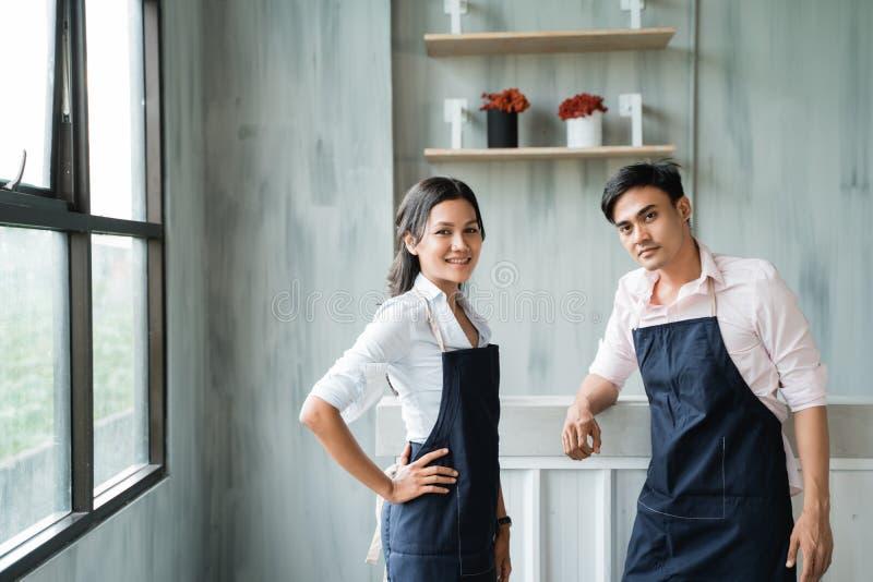 Mooie en knappe kelners die zich vooraan het lijstbar glimlachen bevinden royalty-vrije stock foto
