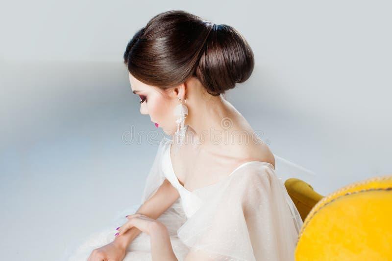 Mooie en modieuze bruid in huwelijkskleding in Studiozitting als voorzitter stock fotografie