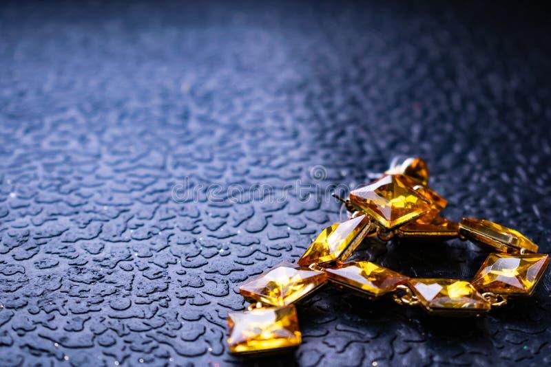 Mooie en modieuze juwelen en toebehoren voor vrouwen Gele, oranje stenen met vierkante stenen op donkere en houten geweven bedela royalty-vrije stock afbeeldingen