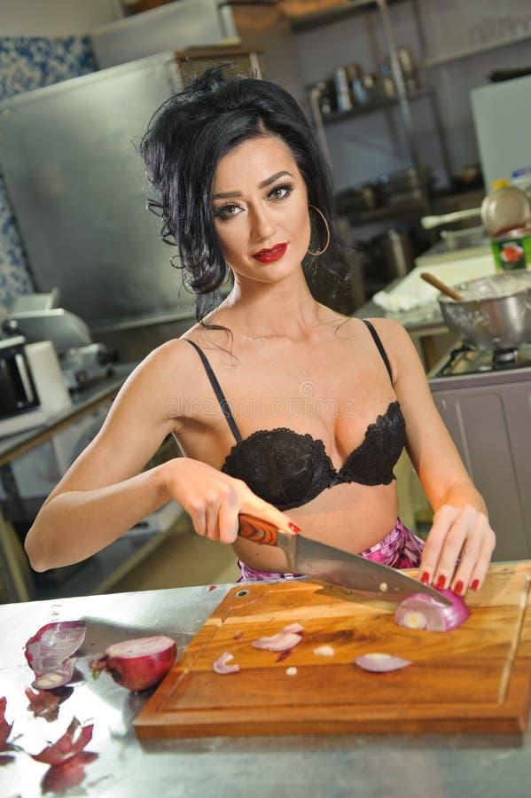 Mooie en sexy vrouw in de keuken Het glimlachen brunette die voedsel voorbereiden Jong meisje die zwarte bustehouder dragen die s stock afbeeldingen