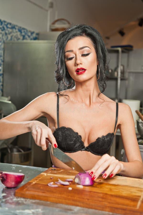 Mooie en sexy vrouw in de keuken Het glimlachen brunette die voedsel voorbereiden Jong meisje die zwarte bustehouder dragen die s royalty-vrije stock afbeelding