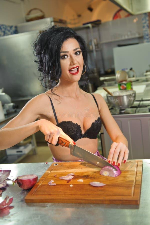 Mooie en sexy vrouw in de keuken Het glimlachen brunette die voedsel voorbereiden Jong meisje die zwarte bustehouder dragen die s royalty-vrije stock fotografie
