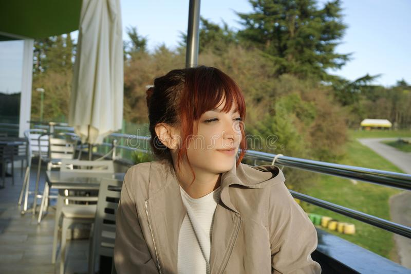 Mooie en slimme jonge vrouwenzitting op het koffieterras en tevreden onderzoekend de afstand royalty-vrije stock foto