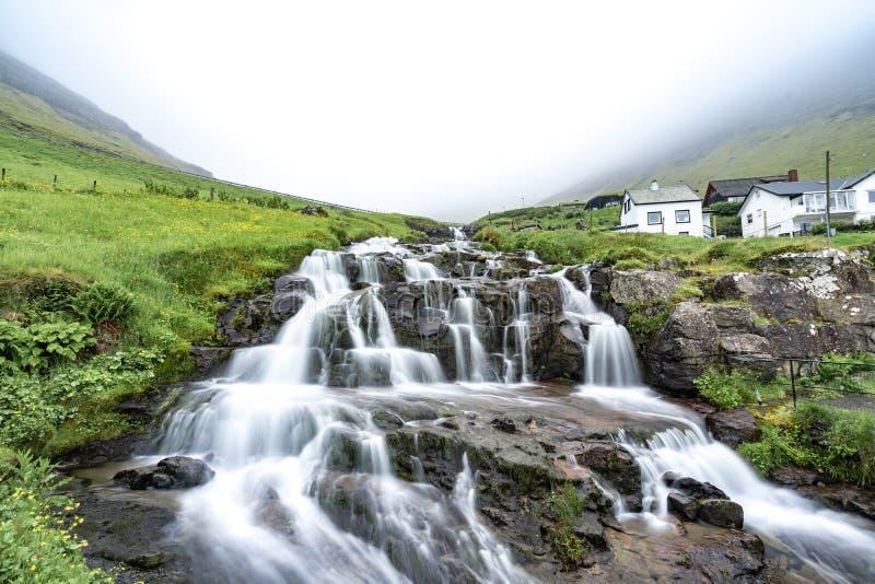 Mooie en vreedzame waterval lange blootstelling met groene gras stock afbeeldingen