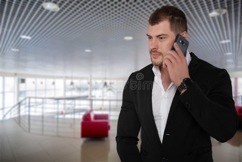 Mooie ernstige bedrijfsmens in kostuum met smartphone in modern bureau stock afbeelding