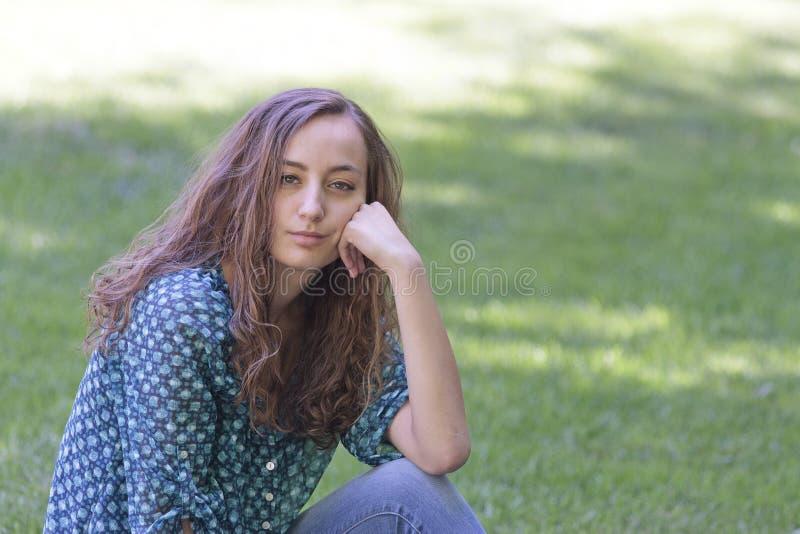 Mooie, ernstige, jonge vrouwenzitting op gras royalty-vrije stock foto