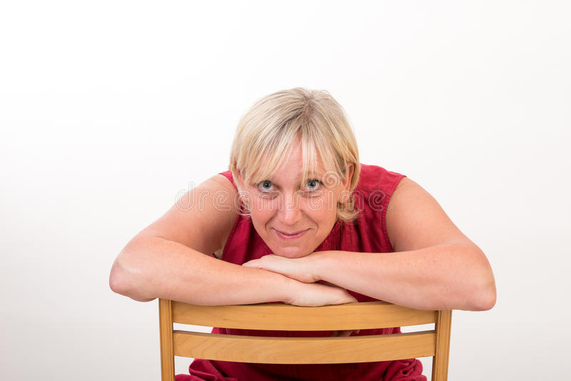 Mooie Europese medio oude vrouw in rode kleding zitting ontspannen o stock fotografie