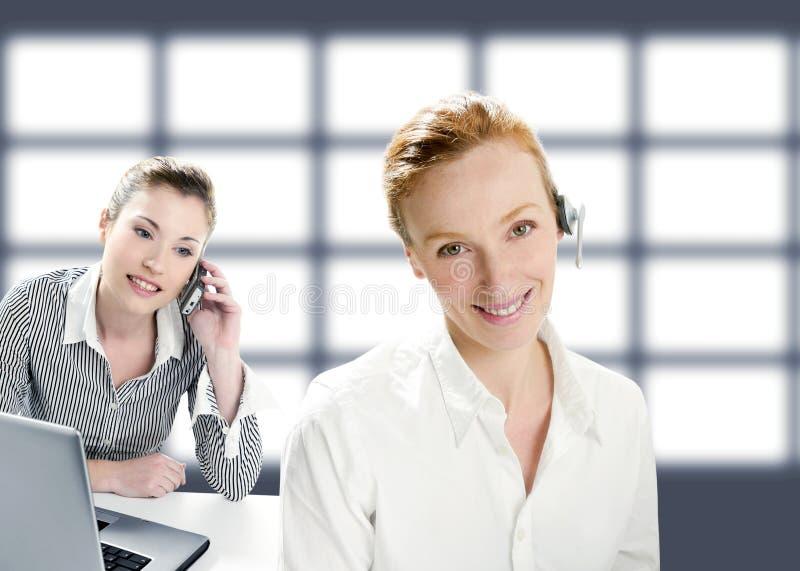 Mooie exploitantvrouwen die en telefoon glimlachen spreken royalty-vrije stock afbeeldingen