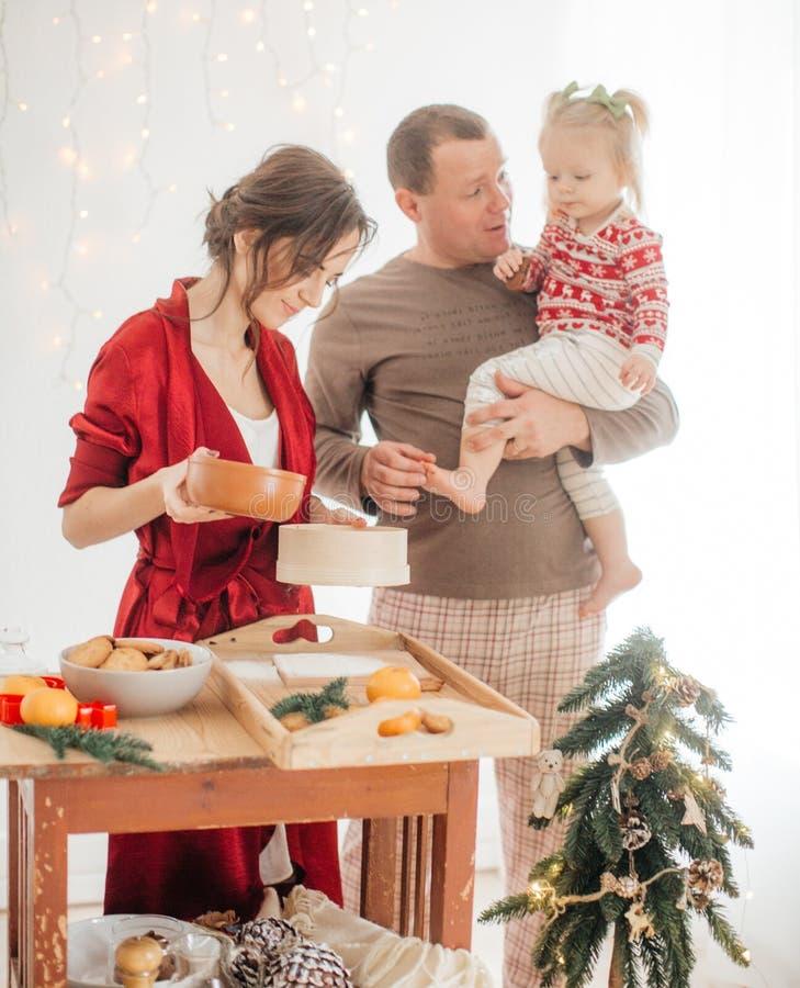 Mooie familie met babymeisje die het deeg voor de pastei voorbereiden royalty-vrije stock afbeelding