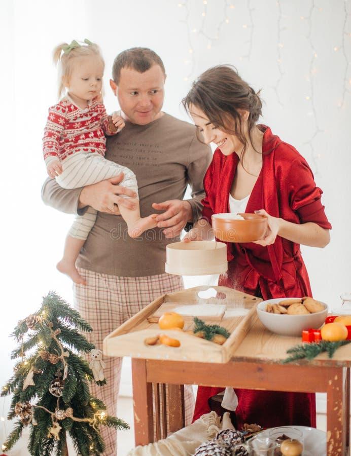 Mooie familie met babymeisje die het deeg voor de pastei voorbereiden stock foto