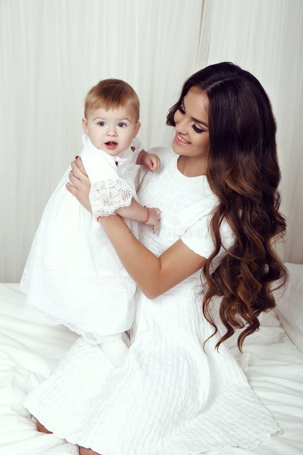Mooie familiefoto schitterende moeder met haar weinig leuk babymeisje stock foto