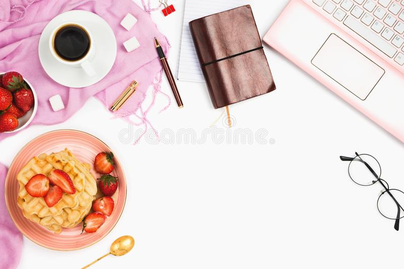 Mooie flatlay regeling met kop van koffie, hete wafels met room en aardbeien, laptop en andere bedrijfstoebehoren royalty-vrije stock foto